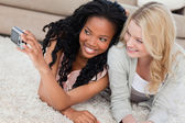 Two women lying on the floor are posing for a picture — Stock Photo