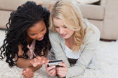 Two women are looking through photos on a digital camera — Stock Photo