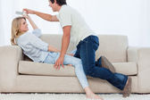 A man tries to get the television remote control off his girlfri — Stock Photo