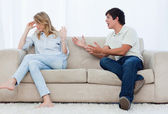 A man is having an argument with his girlfriend while sitting on — Stock Photo