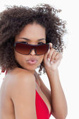Young woman puckering her lips while holding her sunglasses — Stock Photo