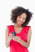 Smiling young brunette woman holding a mobile phone — Stock Photo