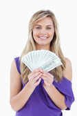 Happy blonde woman holding a fan of notes — Stock Photo