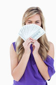 Blonde woman blinking an eye while holding bank notes — Stock Photo