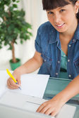 Portrait of a cute smiling student doing her homework — Stock Photo