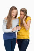 Two females student smiling while looking a cellphone — Stock Photo