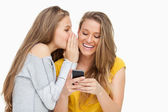 Young woman whispering to her friend who's texting on her phone — Stock Photo