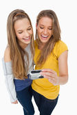 Two friends laughing while checking their picture on a digital c — Stock Photo