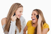Close-up of two young women laughing on the phone — Stock Photo