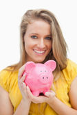 Close-up of a piggy-bank holding by a blond woman — Stock Photo
