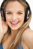 Portrait of a beautiful young blonde wearing headphones — Stock Photo