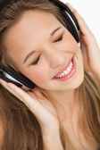 Close-up of a cute young blonde listening to music — Stock Photo