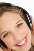 Close-up of a green-eyes woman listening to music — Stock Photo