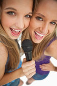 High-angle shot of two happy young beauty singing — Stock Photo