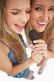 High-angle shot of two happy young blonde singing — Stock Photo