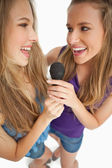 High-angle shot of two happy young beauty singing together — Stock Photo