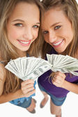 High-angle shot of two happy young beauty holding dollars — Stock Photo