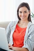 Close-up de uma mulher usando seu laptop e olhando para a câmera — Fotografia Stock