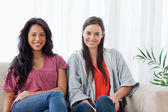Two smiling women sit on the couch together while looking at the — Stock Photo
