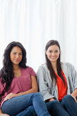 Half length shot of two women on the couch looking into the came — Stock Photo