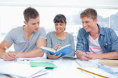 Two students getting help from a female student — Stock Photo