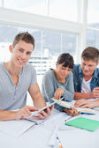 Two students use a book while the student using a tablet looks a — Stock Photo