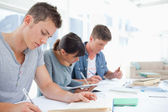 Side view of three students quietly working together — Stock Photo