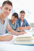 A close up of three studying friends as they look into the camer — Stock Photo