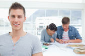 Student standing in front of his fellow students and smiling — Stock Photo