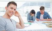 Um estudante sorridente senta-se na frente de seus amigos como ele olha para — Foto Stock
