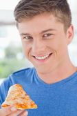 Close up of a man with pizza as he gets ready to eat it — Stock Photo
