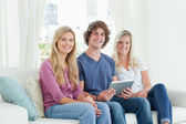 Three young adults look at the camera as they hold a tablet in t — Stock Photo