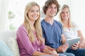 Três sorrindo juntos sentarcom no sofá com um tablet — Foto Stock