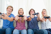 A group of friends all playing video games together and smiling — Stock Photo