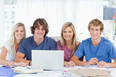 A group of students with a laptop look into the camera — Stock Photo