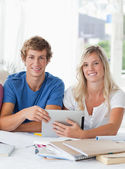 A smiling couple hold a tablet as they both look into the camera — Stock Photo