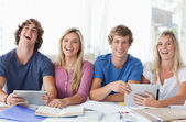 Two couples sit together and work with the help of tablet pc's — Stock Photo