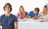 A young man sitting in front of his working class mates — Stock Photo
