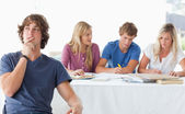 A young man sitting in front of his working class mates and thin — Stock Photo