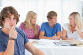 Close up of a thinking man sitting in front of his friends — Stock Photo