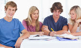 Four friends sitting at the table and studying — Stock Photo