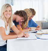 A smiling girl looks at the camera as her friends study — Stock Photo