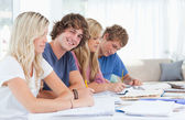 Students studying together with one man looking at the camera an — Stock Photo