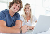 A smiling couple with a laptop looking at the camera — Stock Photo