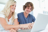 A smiling couple using a laptop while pointing at the screen — Stock Photo
