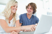 A couple use a laptop with a man looking at the woman — Foto Stock