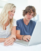 A smiling couple sitting and using the laptop — Foto Stock