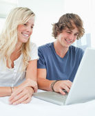A smiling couple sit together as they surf the internet — Stock Photo