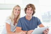 A smiling couple holding a tablet and looking at the camera — Stock Photo