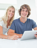 Close up smiling couple holding a tablet and looking at the came — Stock Photo